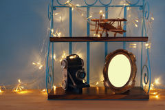 Vintage shelf with old wooden plane toy, decorative camera and blank photo frame Stock Photo