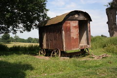 Vintage shepherds hut. Old vintage shepherds hut on wonky wheels rusting in field, bright sunny day Stock Images