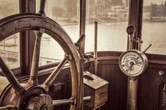 Vintage ship steering wheel in sepia toning. Steering wheel and engine controls telegraph on a vintage ship bridge, retro sepia toning Royalty Free Stock Image