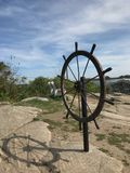 Vintage ship steering wheel. Vintage ship steering wheel on a beautiful landscape in Kenneabunkport, Maine Royalty Free Stock Photos