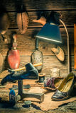 Vintage shoemaker workplace with shoes, laces and tools Stock Image
