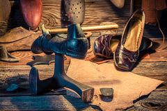 Vintage shoemaker workplace with tools, leather and shoes Royalty Free Stock Images