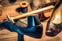 Vintage shoemaker workplace with tools, shoes and leather Royalty Free Stock Photos