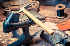 Vintage shoemaker workshop with brush and shoes Stock Photo