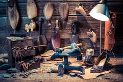 Vintage shoemaker workshop with shoes, laces and tools Royalty Free Stock Image