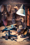 Vintage shoemaker workshop with tools, leather and shoes Stock Photography