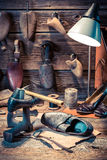 Vintage shoemaker workshop with tools, shoes and laces Royalty Free Stock Photography