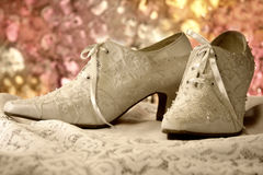Vintage shoes. A pair of beaded, vintage wedding shoes sitting on lace displayed against a pastel abstract background Royalty Free Stock Photography
