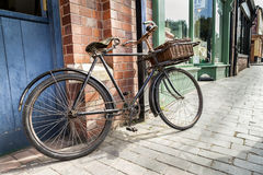 Vintage shop bicycle with wicker basket on the front. Vintage shop bicycle with wicker basket on the front, leaning against a shop wall padlocked and chained Royalty Free Stock Images