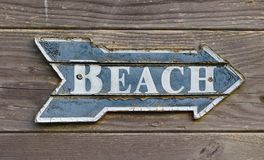 Vintage signpost on a wooden wall saying `Beach`. Vintage blue and white signpost shaped like an arrow saying `Beach` on wooden panel wall stock images