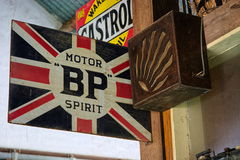 Vintage signs. Vintage metal signs advertising oil and a radio speaker hang from a wall in an old garage. Retro signage is now hugely sought after in the UK and stock photos