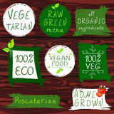 Vintage signs: vegetarian, raw green menu, all organic ingredients, 100 ECO, vegan food, 100 VEG, pescatarian, home. Grown. VECTOR signs on wooden background Royalty Free Stock Images
