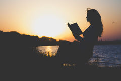 Vintage silhouette of a young beautiful woman at dawn sitting on a folding chair and think about the information which is read Royalty Free Stock Photo
