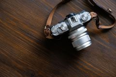 Vintage silver and black camera with brown leather strap on wooden table stock image