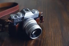 Vintage silver and black camera with brown leather strap on wooden table royalty free stock image