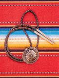 Vintage Silver Bolo Tie on colorful background. Vintage Sterling Silver Bolo Tie with Concho and Silver Tips on colorful southwestern hand woven fabric stock photos