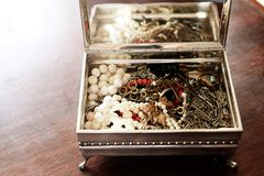 Shiny trinkets in silver box. Vintage silver box open, containing shiny trinkets and jewellery, pearl,necklaces and bracelets royalty free stock photos