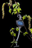 Vintage silver bracelet with blue agate on branch of birch. With buds and leaves isolated on black stock image