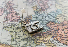 Vintage silver camera pendant pinned to antique map Royalty Free Stock Photo