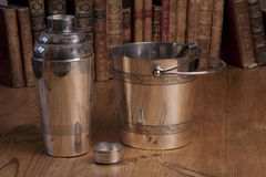 Vintage silver cocktail shaker set. Vintage silver cocktail shaker and icebox standing on a wooden table with a row of books in the background Stock Images