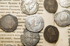 Vintage silver coins with portraits on the book Royalty Free Stock Photo