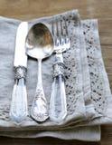 Vintage silver cutlery with linen napkin Stock Photos