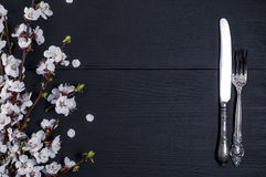 Vintage silver fork and knife. Vintage silver cutlery on a black wooden surface, on the right blossoming cherry branch, empty space in the middle Stock Photos