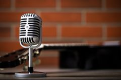 Vintage microphone and guitar. Royalty Free Stock Images