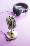 Vintage silver microphone and headphones. The vintage silver microphone and headphones stock photography