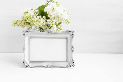 Vintage silver photo frame with lilac flowers on white still lif Royalty Free Stock Photo