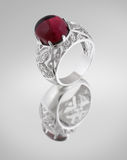 Vintage silver ring with red gem. On grey Royalty Free Stock Photos