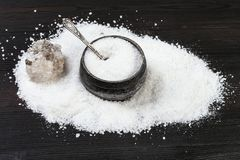 Vintage silver salt cellar and raw Halite on table. Vintage silver salt cellar with spoon, rough natural Halite mineral and grained Rock Salt on dark brown royalty free stock image