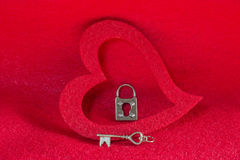 Vintage silver skeleton key and lock in a red heart background Royalty Free Stock Image