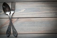 Vintage silver spoon and fork on a wooden background. Kitchen utensils. royalty free stock images
