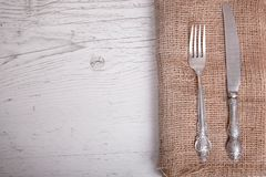 Vintage silver tableware knife and fork is on napkin, on an old. Table stock image