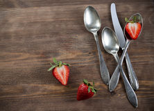 Vintage silverware on brown table with strawberry country style. Old spoons and knife on wooden surface with strawberry for invitation and menu Royalty Free Stock Photos