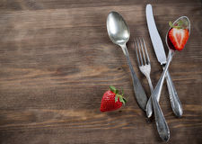 Vintage silverware on brown table with strawberry. Old spoons, fork, knife on wooden surface and fresh red strawberry Stock Photo