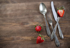 Vintage silverware on brown table with strawberry. Old spoons, fork and knife on wooden surface with strawberry for invitation and menu Royalty Free Stock Photos