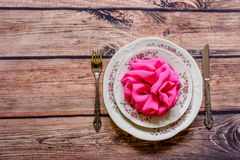 Vintage silverware and china with pink decoration on rustic wood Stock Photo