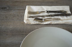 Vintage silverware. And dishware on old wooden table, country style in low natural light Stock Photography