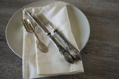 Vintage silverware. And dishware on old wooden table, country style in low natural light Royalty Free Stock Images
