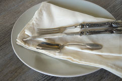 Vintage silverware. And dishware on old wooden table, country style in low natural light Royalty Free Stock Photography