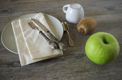 Vintage silverware and dishware. On old wooden table, country style in low natural light with a green apple, a coffee cup and a brown kiwi Royalty Free Stock Images