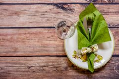 Vintage silverware on a green napkin on a plate and wineglass on Stock Photography