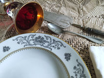 Vintage silverware and porcelain plates. With a goblet Royalty Free Stock Images