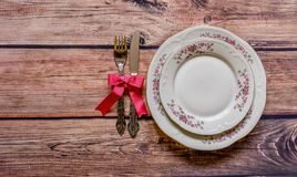 Vintage silverware tied with pink bow and chine on rustic wooden Stock Image