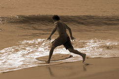 Vintage simboarding. Young male preparing to Skimboard along beach royalty free stock images
