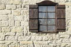 Vintage Single Window  with Wooden Shutters on Natural Stone Wal Stock Photos