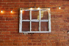 Vintage Six Pane Window. Used as interior/exterior decoration on red brick wall with string of accent lights royalty free stock photos