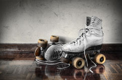 Vintage Skates. Vintage roller skates with big shoe-laces on a dirty wall background Royalty Free Stock Photo